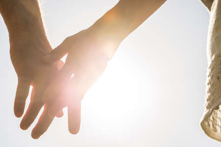 husbands and wives: Romantic couple with clasped hands backlit by a bright evening sun in a closeup conceptual image of love, commitment and friendship. Stock Photo