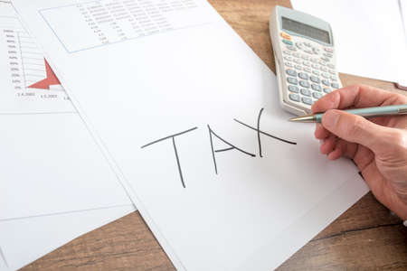 hand paper: Close up Human Hand Writing Tax on a White Paper on Top of a Wooden Table with Calculator and Report Documents. Stock Photo