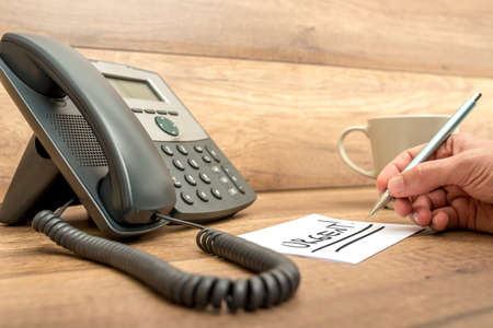 Closeup of male receptionist writing the word Urgent twice underlined on a white card next to a landline telephone.