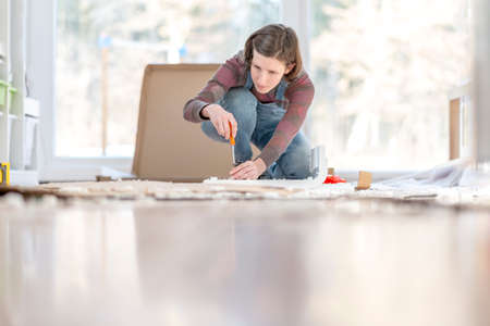 Young Woman assembling a DIY furniture at home kneeling on the floor in front of a bright glass window surrounded by materials and tools working with a screwdriver. Focus on the screwdriver.