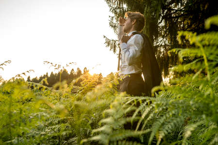 primal: Young Businessman Holding is Coat Over his Shoulder, Standing in the Forest and Looking into the Distance at the Afternoon. Stock Photo