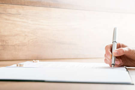 mariage: Signature contrat de mariage ou des papiers de divorce avec deux anneaux de mariage chaque couché sur un côté du document. Banque d'images