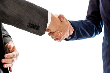 conclude: Confident businessman shaking hands with his  female business partner to conclude a deal, agreement, partnership or in congratulations over white background.