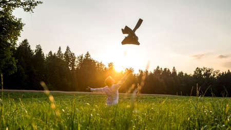 Happy Businessman at the Green Field Throwing his Coat with Wide Open Arms to Celebrate Success During Sunset Time. Standard-Bild