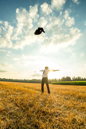primal: Successful Young Businessman in an Open Field, Throwing his Coat in the Air with Arms Wide Open Against Sunlight.