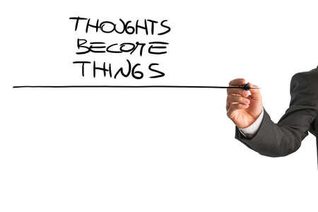 thoughts: Closeup of consultant underlining a Thoughts become things proverb from behind a white virtual screen explaining how powerful and creative your thoughts are. Stock Photo