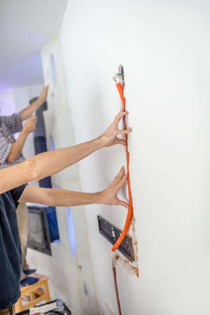 workmen: Workmen doing home maintenance or renovation with an electrician seating a cable into a recessed groove in the wall while a second man works in the background.