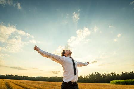 La metà del corpo ha sparato di un giovane uomo d'affari riconoscente che osserva in su il cielo con le braccia spalancate, levantesi in piedi al campo aperto. Archivio Fotografico
