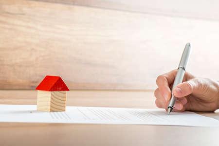 firmando: Primer plano de nuevo propietario firma de un contrato de venta de la casa o papeles de la hipoteca con una casa de juguete de madera en el documento. Adecuado para el concepto de bienes raíces.