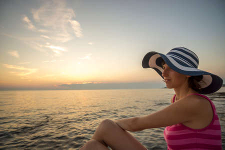 evening glow: Stylish young woman in a trendy straw sunhat relaxing on a sunset beach looking out over the calm ocean back lit by the glow of the sun, profile view.