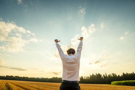 Half Body Rear View of a Successful Young Businessman Raising his Arms with Thumbs Up Hand Signs at the Open Field During Sunset Time. Standard-Bild
