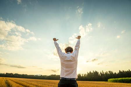 Metà corpo vista posteriore di un uomo d'affari di successo giovane alzando le braccia con i pollici fino segni mano al campo aperto durante il tramonto tempo. Archivio Fotografico - 43222849