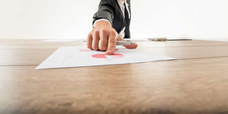 finger pointing: Low angle wide angle view with receding perspective of a businessman pointing to an analytical pie graph on a wooden desk with his finger.
