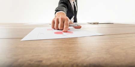 dedo apuntando: Vista gran angular de bajo ángulo con retroceso perspectiva de un hombre de negocios que apunta a un gráfico circular analítico sobre un escritorio de madera con el dedo.
