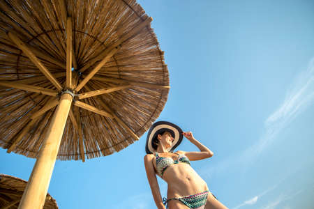 sun umbrella: Low angle view looking up from the ground of a shapely woman in a bikini enjoying a summer vacation on a tropical beach alongside a thatch beach umbrella at a resort.