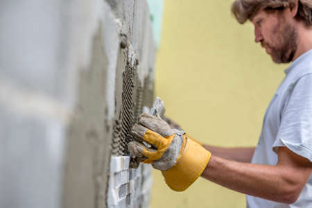 lining up: Builder tiling a concrete wall with decorative ornamental tiles lining up a tile with his gloved hands to seat into the tiling cement on the wall, profile view along the length of the wall. Stock Photo