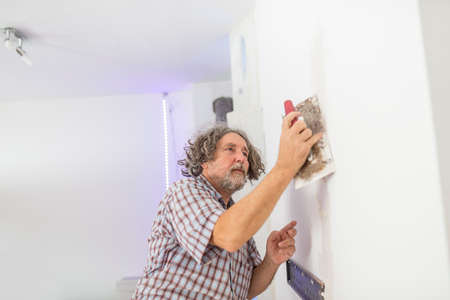 homeowner: Middle-aged male builder or homeowner plastering a white wall preparing it for painting as he repairs a crack or opening in a DIY and home decoration or renovation concept. Stock Photo