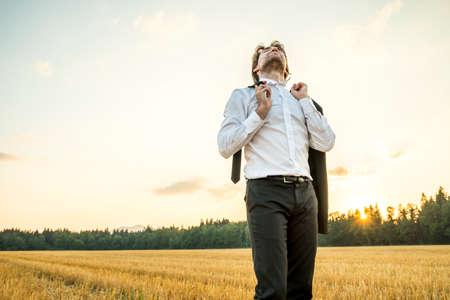 iluminado a contraluz: Relajado empresario en camisa blanca que se coloca en campo de trigo que sostiene la chaqueta del traje en una mano y la corbata en otro, celebrando la vida, el éxito y el objetivo de negocio logrado, iluminado por el sol de la tarde. Foto de archivo