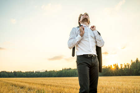 relieved: Relaxed businessman in white shirt standing in wheat field holding suit jacket in one hand and tie in another, celebrating life, success and accomplished business goal, backlit by the evening sun.