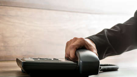 hang up: Male hand with black sleeve suit picking up the receiver of an office telephone, with copy space on rustic wooden background. Concept of customer support, global communication and telemarketing. Stock Photo