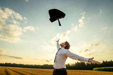 Feliz exitoso joven empresario arrojando su abrigo en el aire por estar libre de algo con los brazos abiertos en el campo durante el atardecer.