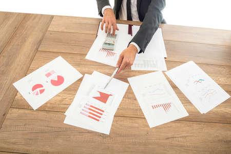 Hombre de negocios dando una presentación con gráficos analíticos y gráficos variados extendido sobre la mesa frente a él apuntando a la información relevante con una pluma.