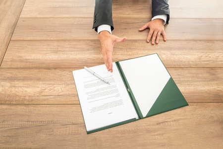 Businessman waiting to shake hands over a contract laid out for signature on the desk in front of him in a conceptual image, close up high angle of the paperwork and hand. Reklamní fotografie