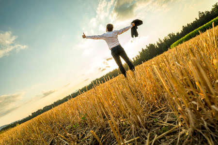 Rear View of a Successful Young Businessman Standing at the Field with Wide Open Arms and Looking Up in the Sky.