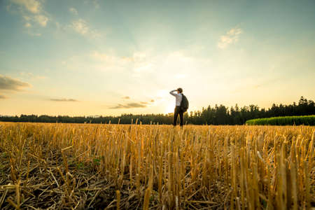 personal perspective: Rear View of a Young Businessman Standing at the Field, Looking Into the Distance During Sunset Time. Stock Photo