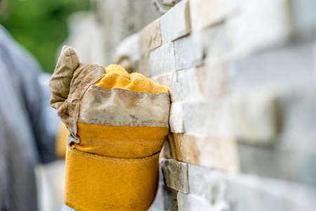 Closeup of manual worker in protection gloves  tiling a wall with ornamental tiles pushing the tile into the cement on the wall in a DIY, renovation or construction concept.
