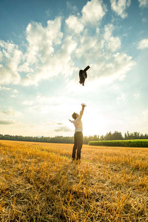 stress free: Happy Successful Young Businessman Throwing His Coat Up in the Air at the Open Field During Sunset. Stock Photo