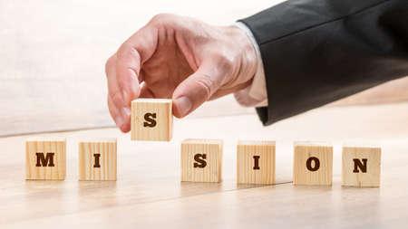 7 나무 큐브와 word 임무를 만드는 사업가의 근접 촬영. 비즈니스 비전, 목표 및 전략의 개념.