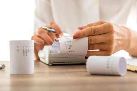 Frau tun Berechnungen auf einer Rechenmaschine oder Rechner Abziehen Ries Papier mit aufgedruckten Zahlen und Summen, konzeptionelle der Rechnungslegung eine Buchhaltung, Nahaufnahme von ihren Händen.
