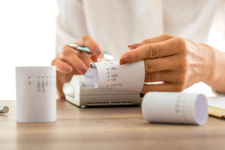 the conceptual: Woman doing calculations on an adding machine or calculator pulling off reams of paper with printed figures and totals, conceptual of accounting a bookkeeping, close up of her hands. Stock Photo