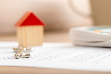 Closeup of contract of house sale ready to be signed with wooden toy house, house key and calculator on it. Conceptual of real estate, mortgage and lease.