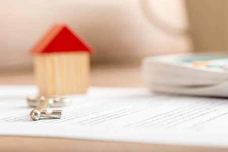 contratos: Primer plano de contrato de venta casa listo para ser firmado con la casa de juguetes de madera, llave de la casa y calculadora en ella. Conceptual de bienes raíces, hipotecas y arrendamiento. Foto de archivo