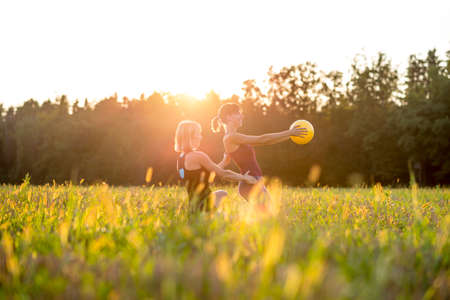 outdoor training: Two young women doing pilates exercises in a rural meadow backlit by the warm light of the rising morning sun over the treetops in a health and fitness concept.