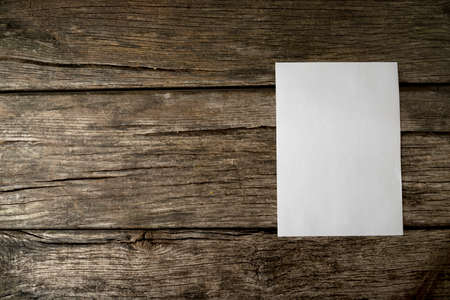 Blank sheet of white paper with copyspace for your text on old textured rustic wooden boards with additional copyspace to the left. Stock Photo
