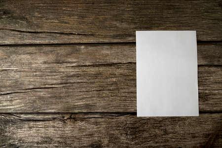 hoja en blanco: Hoja en blanco de papel blanco con copyspace para su texto en viejas texturas rústicas tablas de madera con copyspace adicional a la izquierda.