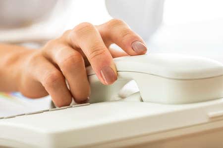 白固定電話の受話器を持って女性の秘書のクローズ アップ。グローバル ・ コミュニケーション、テレマーケティング、ヘルプラインやサポートの