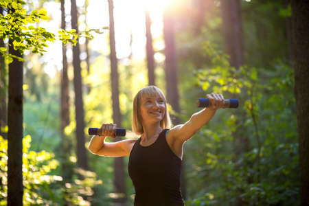 Smiling happy fit young woman working out with weights in a wooded garden or park under the warm glow of the sun in a health and fitness concept. Stock Photo