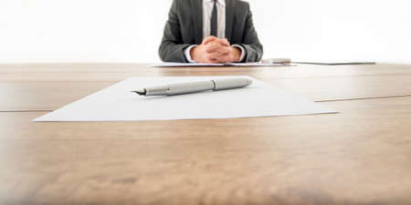 employee: Businessman sitting at his wooden office desk with contract infront of him and another contract opposite to him with a pen waiting to be signed by employee or business partner. Stock Photo