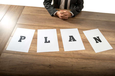 spread the word: Business plan and strategy concept with a businessman sitting at a desk with the word Plan spelt out in letters on individual pages of paper spread out in front of him.
