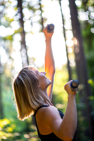 extending: Young blond woman working out outdoors in woodland lifting weights extending the dumbbells to the glow of the sun through the trees with a happy smile. Stock Photo