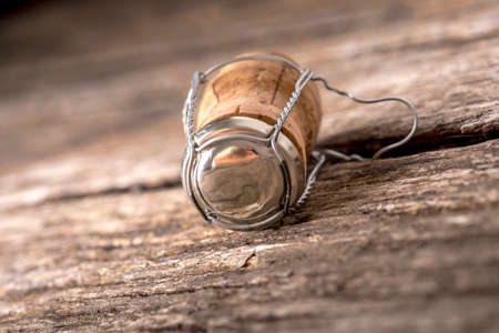 champagne: Champagne cork with attached wire and metal cap lying on old weathered cracked wood boards. Stock Photo