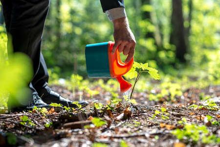 Geschäftsmann in einer Klage, die eine Anlage im Wald mit einem kleinen Plastikspielzeug Gießen Gießkanne in einem konzeptionellen Bild.