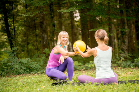 women working out: Two happy smiling women working out exercising in the garden doing pilates exercises together on a green lawn backed by trees and woodland. Stock Photo