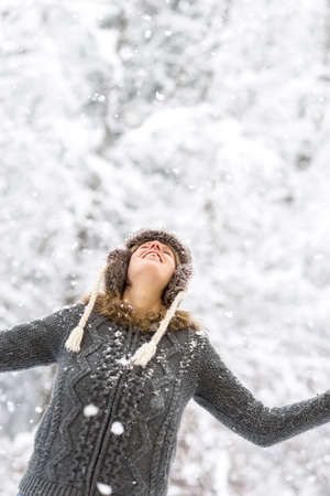 joy: Joyful woman enjoying the winter snow looking up into the falling snowflakes with a happy smile and her arms extended, against a background of snowy vegetation.