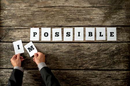 resistencia: Empresario quitando cartas de mensajer�a instant�nea de la palabra imposible cambiar en posible deletreado en tarjetas blancas individuales situadas en escritorio de madera vieja agrietada. Conceptual de la actitud positiva.