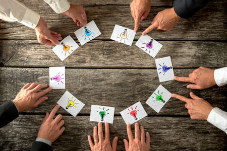 Teamwork and brainstorming concept with businessmen seated around a table each pointing to cards with colorful sketches of light bulbs conceptual of bright ideas and solutions arranged in a circle.
